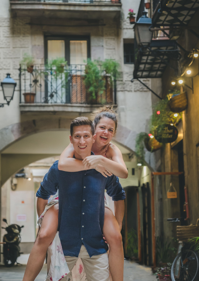 A happy couple doing piggyback in the streets of barcelona