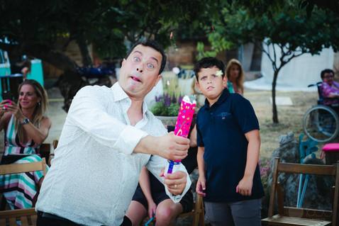 Un invitado a una boda lanza confeti mientras su hijo lo observa sorprendido