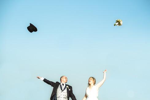 Novio y novia lanzan alegres al cielo sus sombreros y ramillete respectivamente