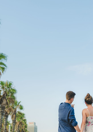 A couple holding hands walks through Barceloneta