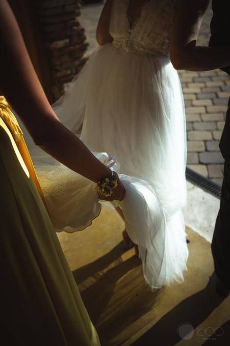 La dama de honor sostiene el vestido de la novia, momentos antes de dirigirse al altar