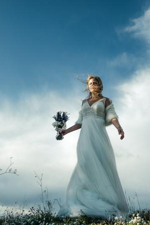 Novia con su pelo al viento y un cielo azul y nubes de fondo