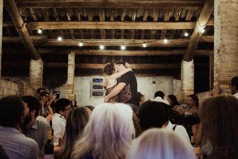 Novios se besan sobre una mesa mientras los invitados alegres los observan