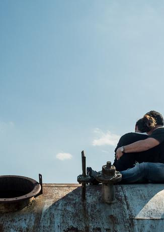 Pareja se abraza mientras se encuentra sentada sobre un barril oxidado