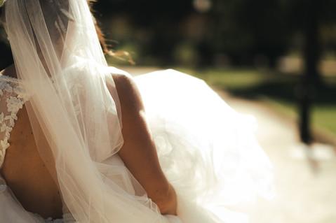 El detalle de la espalda de una novia quien mientras camina, en sus manos recogido lleva el vestido