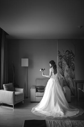 La novia en su vestido y con un ramillete en su mano izquierda, posa para una fotografía en blanco y negro