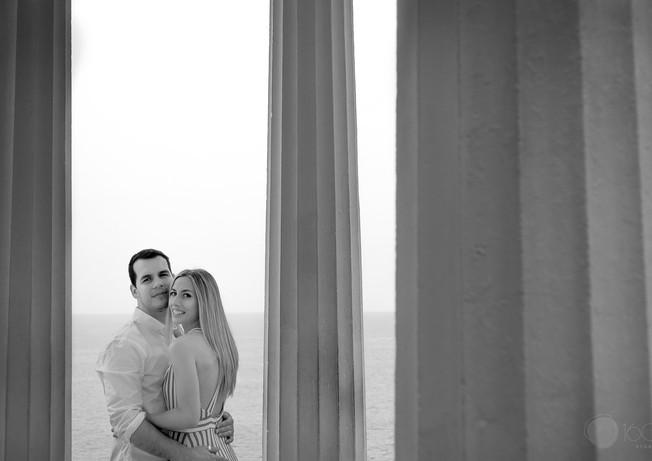Pareja observa a la camara mientras se abrazan con pilares a su alrededor y el mar de fondo