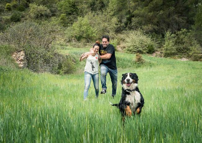 Pareja corre y juega con su perro por la pradera