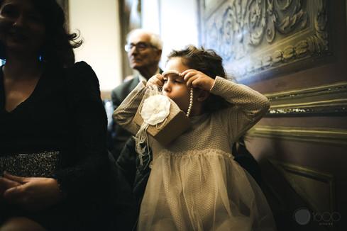 Una niña pequeña juega con su bolsa mientras se desarrolla la boda