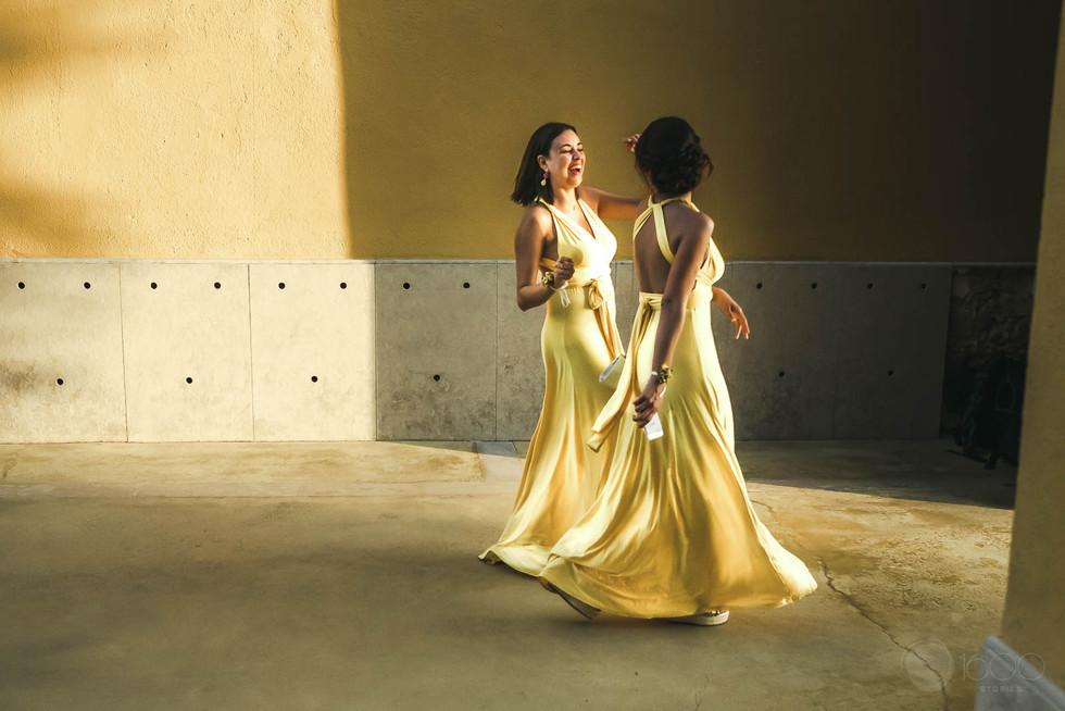 Las damas de honor en vestidos amarillos caminan alegres conversando y riendo