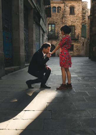 Novio se arrodilla y besa la mano de su novia mientras se encuentran en las calles de El Gotico en Barcelona