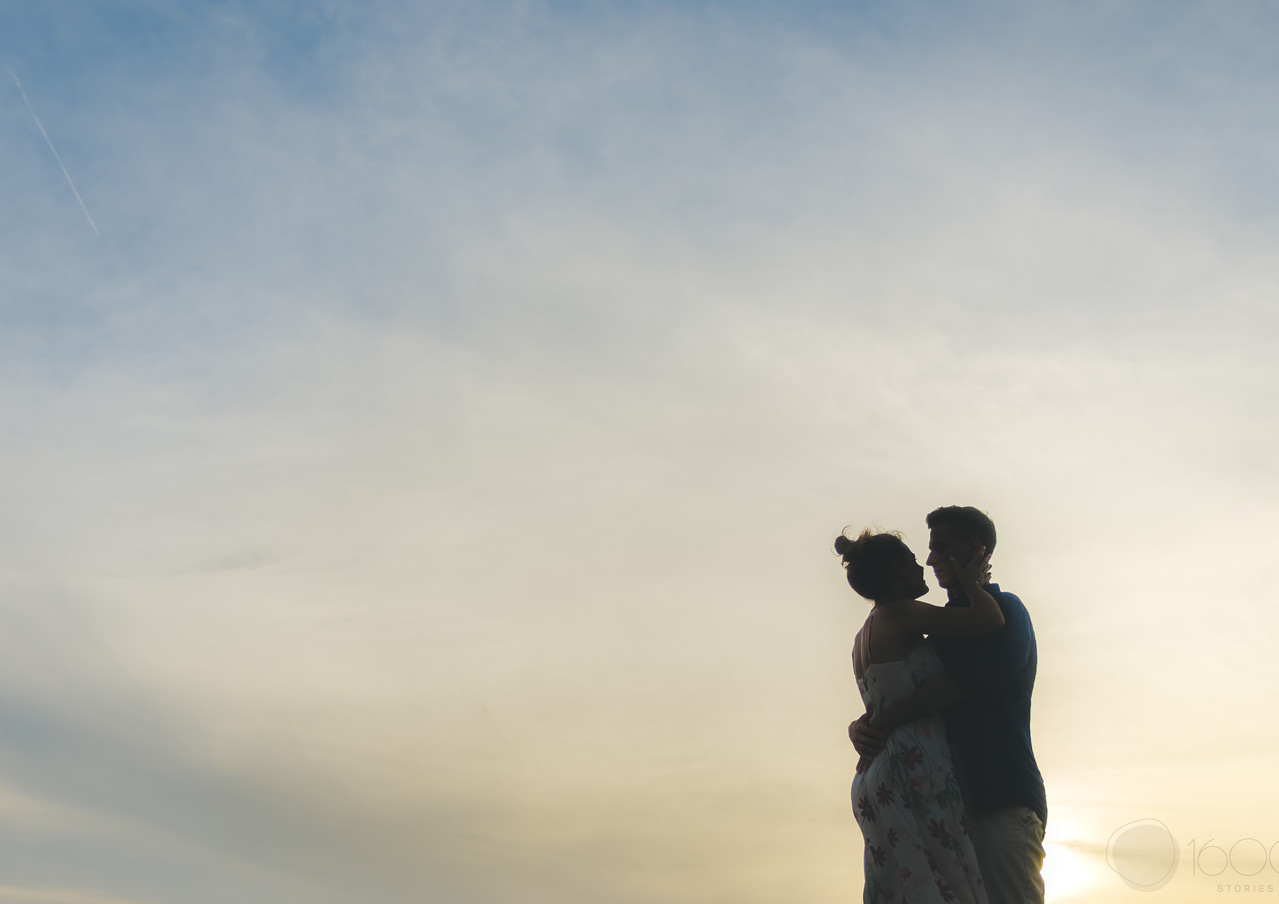 Silhouette of a couple embracing each other with the sky behind