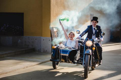 Los novios luego de contraer matrimonio, llegan alegres a la masía en una motocicleta biplaza