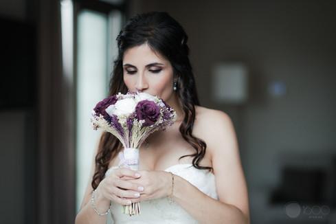 La novia huele el ramillete de flores momentos antes de dirigirse a la ceremonia de bodas