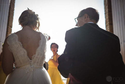 La novia junto a su padre, esperan el momento para dirigirse al altar, una dama de honor loos observa con emoción