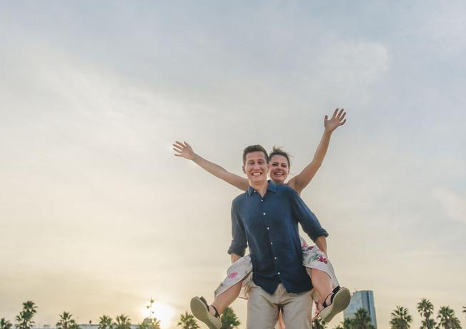 A happy couple doing piggyback at Barceloneta beach