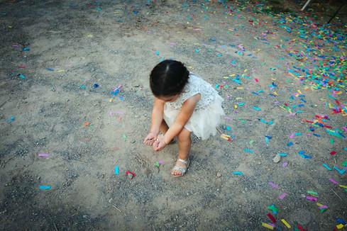 Una niña pequeña juega con el confeti lanzado durante la celebración de una boda