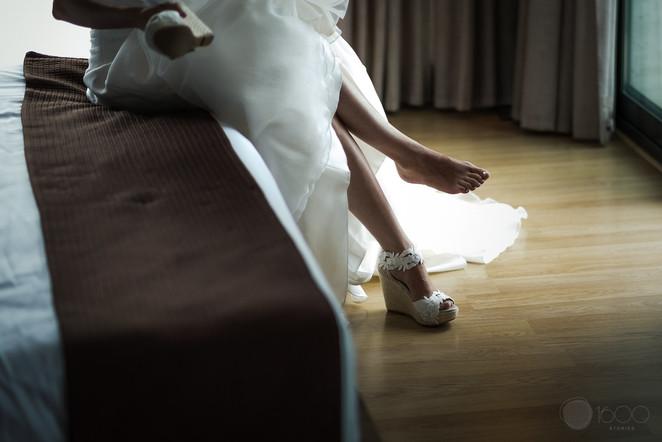 La novia se viste y se calza sus zapatos al borde de la cama del hotel
