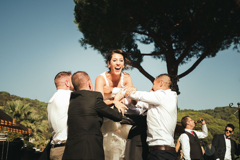 Una novia sonriente salta a los brazos de sus invitados quienes la reciben en los aires