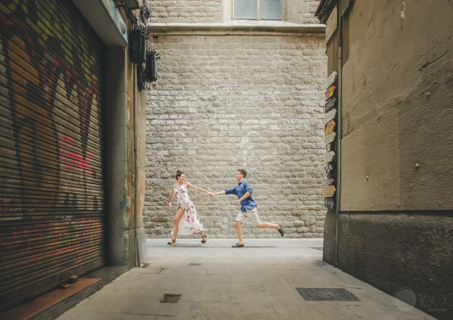 Boyfriend happily chases the girlfriend through the streets of Barcelona