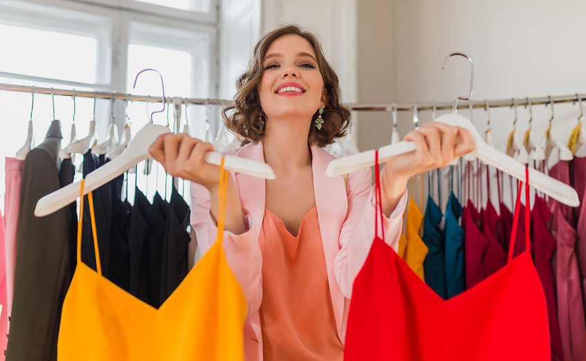attractive stylish smiling woman choosing apparel in clothing store, elegant style, spring