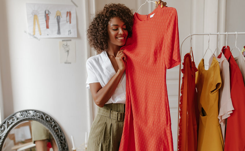 Curly brunette dark-skinned woman in white blouse and khaki shorts smiles widely and holds