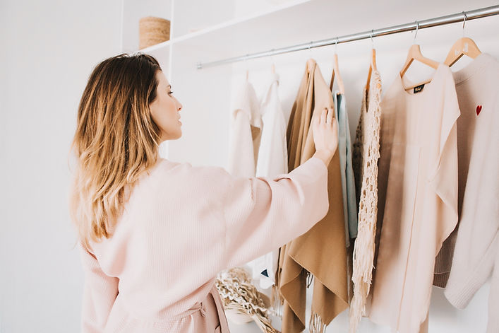 Cute young woman in bathrobe standing in front of hanger rack and trying to choose outfit