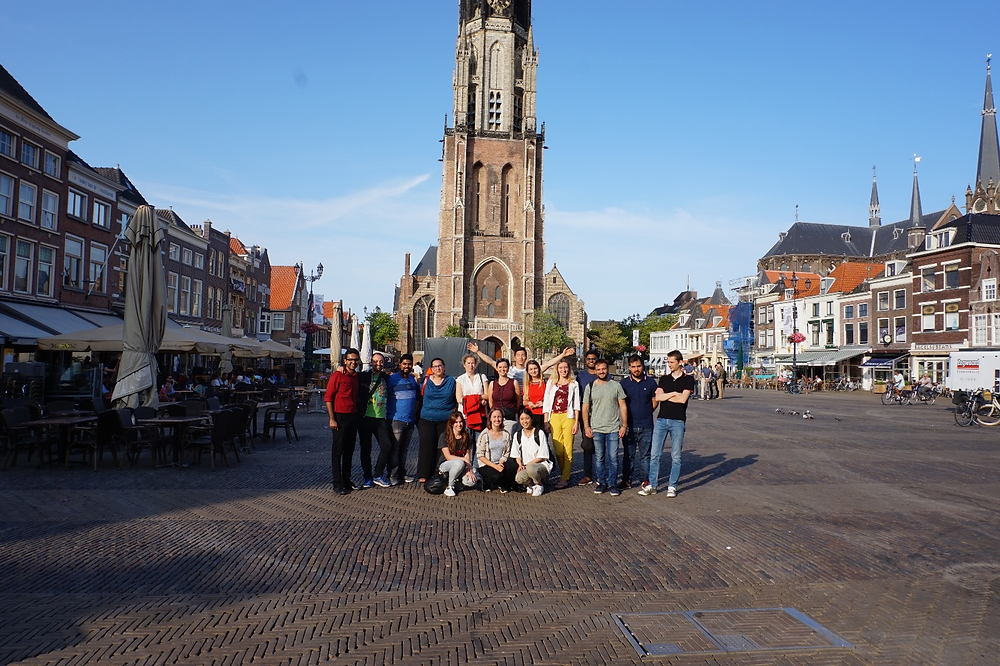 Group photo of the ESRs and organizers in the market square in Delft.