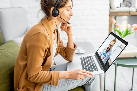 Lady working on her laptop wearing headphones