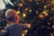 Baby einen Weihnachtsbaum bewundern
