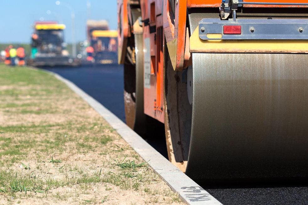 Road roller compacting asphalt  near cur