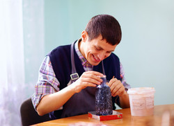 young adult man with disability engaged in craftsmanship on practical lesson, in rehabilitation cent
