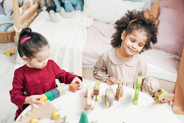 girls-playing-on-a-white-table-3662668.j