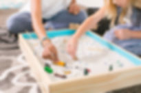 Play therapist and child in sand tray