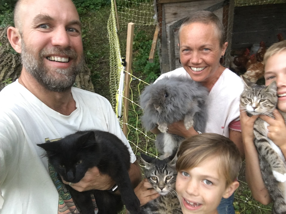 Author with hair growing back holding a fluffy gray bunny, husband holding black kitten, each son holding a kitten, and chickens in a coop in the background.