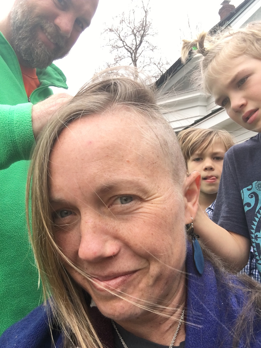 Husband and two sons are shaving the author's hair with an electric razor.