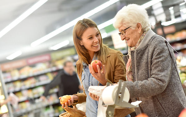 home carer helping an elderly lady complete her shopping in a supermarket.  They are looking at fresh fruit and have fresh bread in their basket
