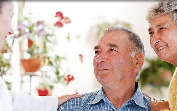 a home carer is talkingto an elderly couple.  the elderly lady is a carer while the man requires care.  the home carer is speaking to them about respite care