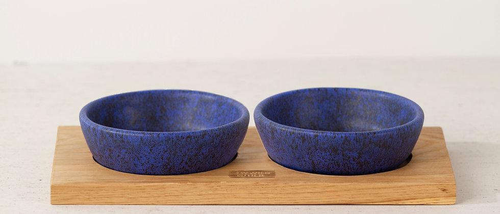Pair of matte blue handmade ceramic dog bowls with oak tray