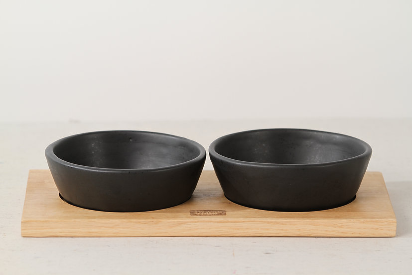 Pair of matte black handmade ceramic cat bowls with oak tray