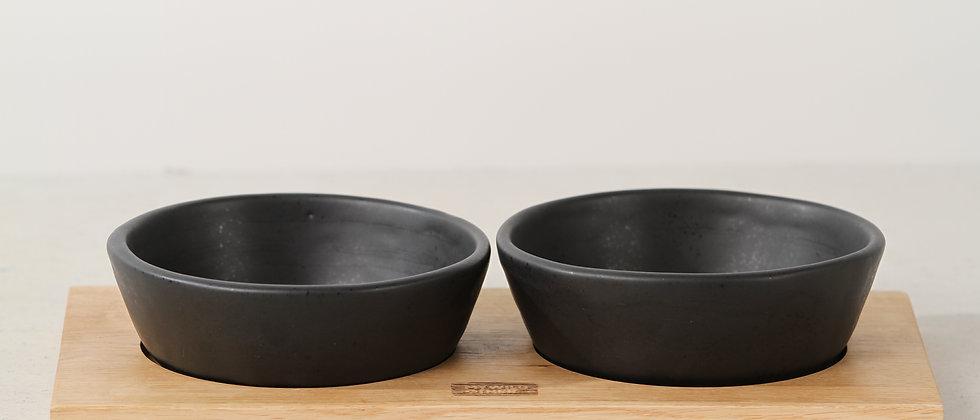 Pair of matte black handmade ceramic cat bowls with oak tray