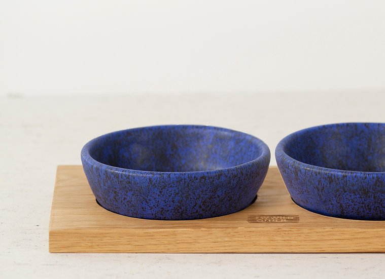 Pair of matte blue handmade ceramic cat bowls with oak tray
