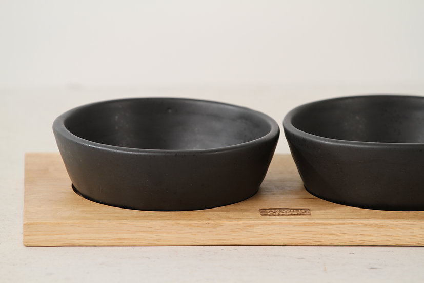 Pair of matte black handmade ceramic dog bowls with oak tray