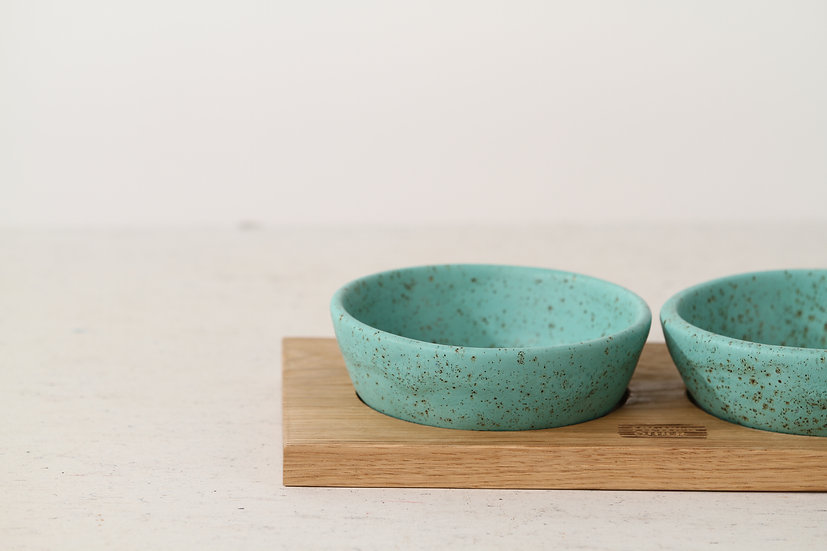 Pair of turquoise handmade ceramic dog bowls with oak tray
