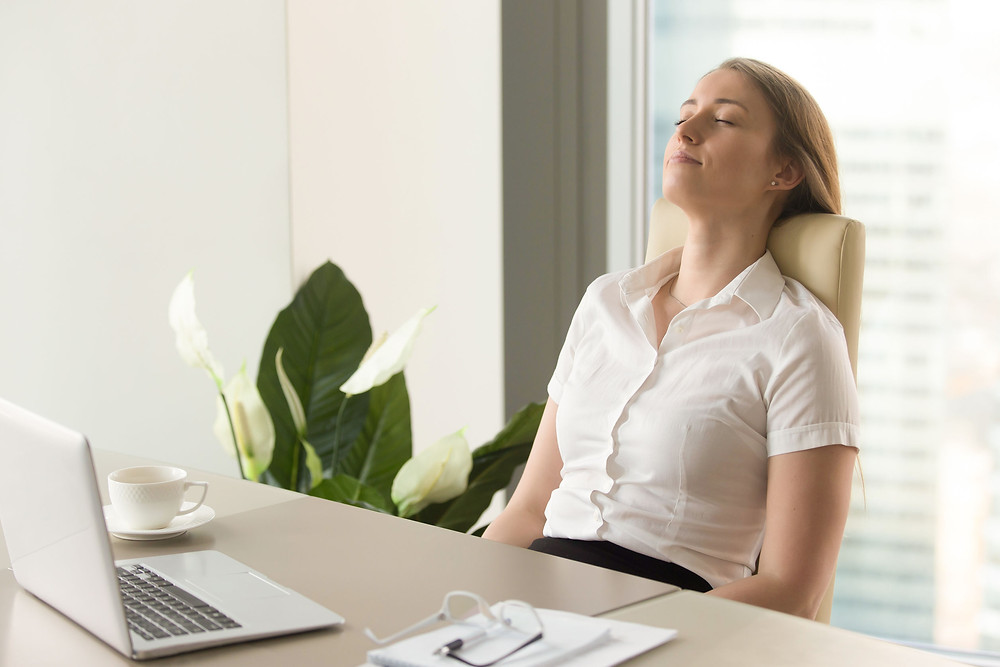 Woman on chair taking a break at her desk with eyes closed.