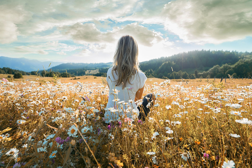 Woman sitting in a field of daisies