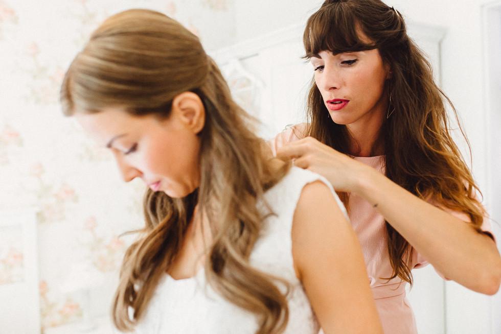 Schwester der Braut hilf beim Anziehen des Hochzeitskleides