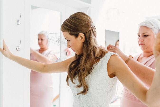 Brautjungfer hilf Braut beim Anziehen