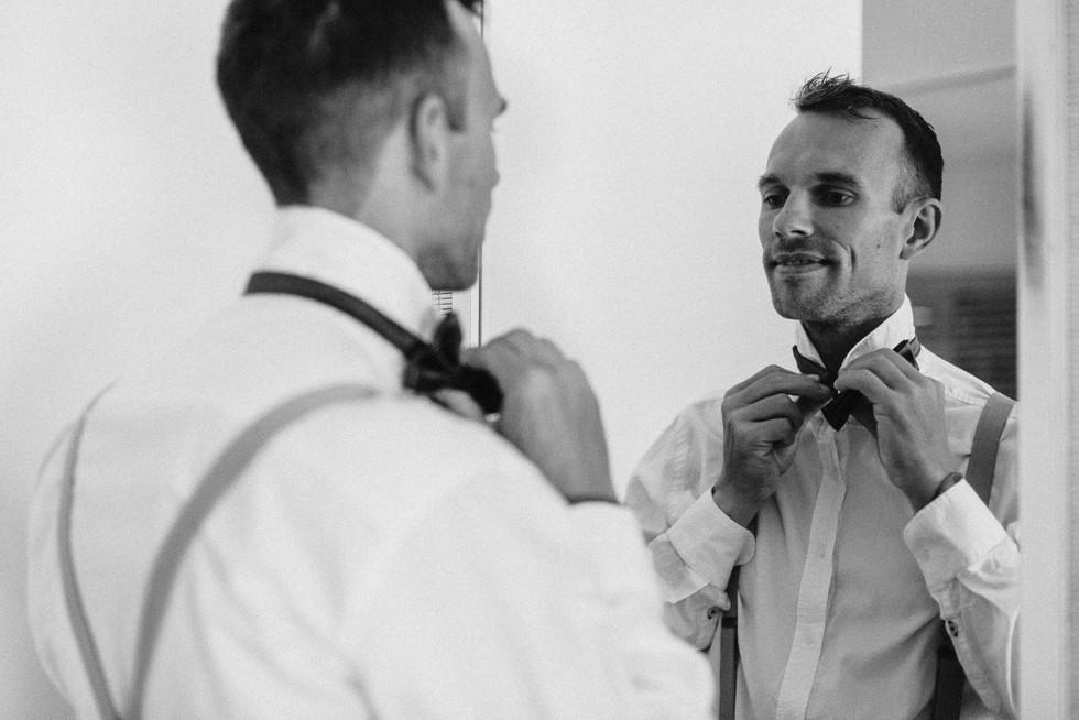 Bräutigam legt Fliege vor dem Spiegel an