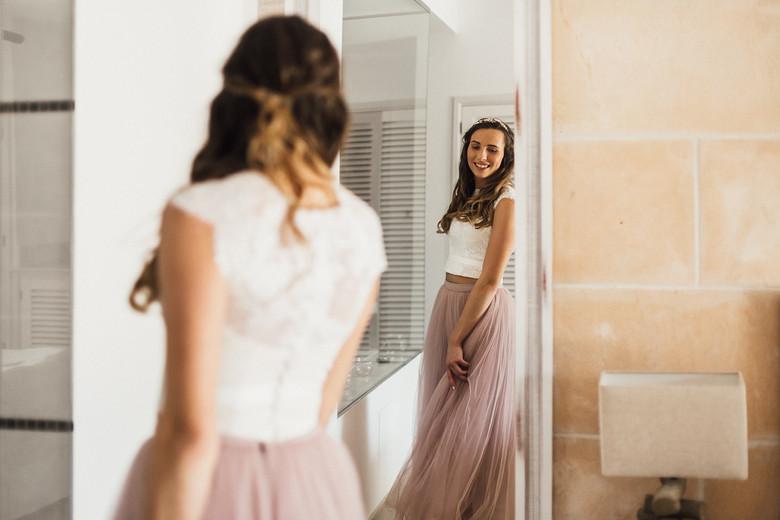 Braut betrachtet sich im Spiegel mit Hochzeitskleid